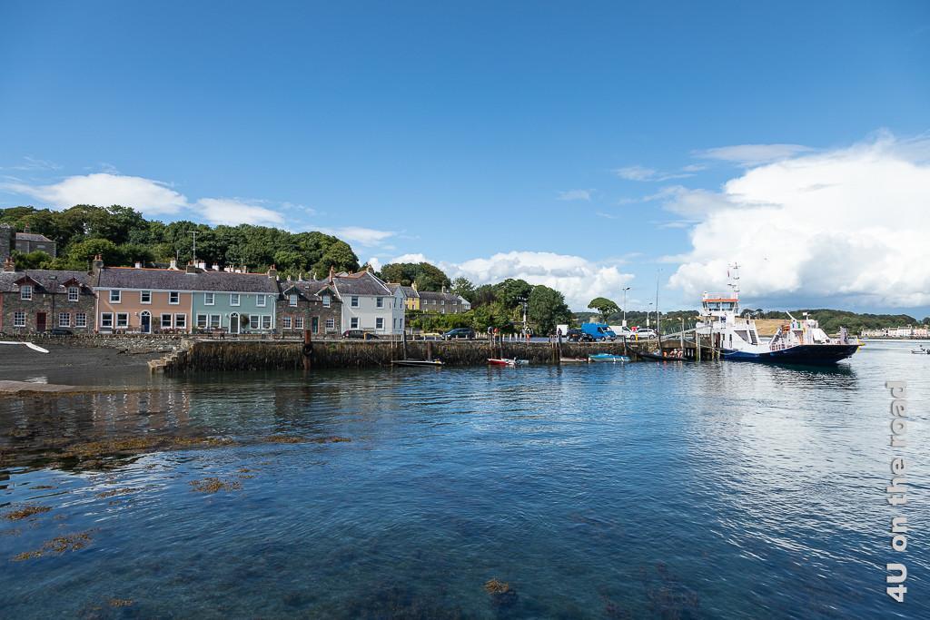 Bild Strangford Hafenfront, zeigt die Hafenpromenade vom Wasser des Stranford Lough aus gesehen mit Hafenmauer und farbigen Häusern und anlegender Fähre.