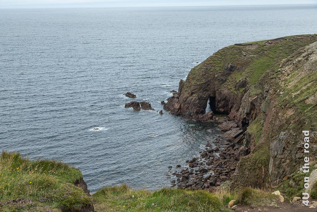 Bild Bloody Foreland Felsküste zeigt einen vom Meer ausgewaschenen Bogen im rötlichen Gestein der Felsklippe