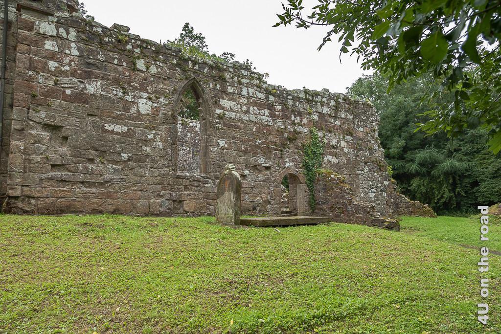 Bild Dungiven Priori zeigt die Kirchenruine von der Seite mit Rundbogen als Eingang und gotischem Fenster. Davor ein Grabstein mit schwerer Grabplatte.