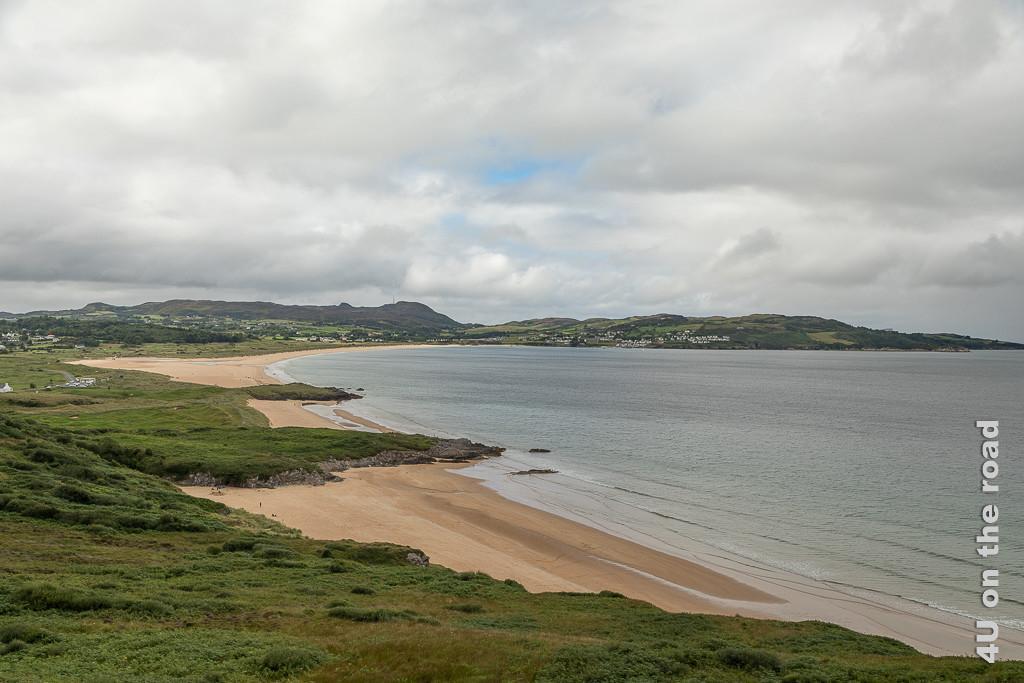 Bild Knockall oder Port Salon Beach, Fanad Peninsula zeigt vom Aussichtspunkt aus den langen Sandstrand in der Bucht, welcher durch Felszungen unterbrochen wird. Auf der gegenüberliegenden Seite der Bucht sieht man Hügel und die Häuser der Stadt.