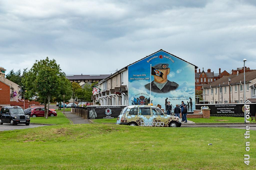 Bild Wohnen mit Gewalt und Gefängnis im Hintergrund, Belfast zeigt die Häuserreihen und das Konterfrei eines Kämpfers im Himmel , an den man sich mit Stolz erinnern soll.