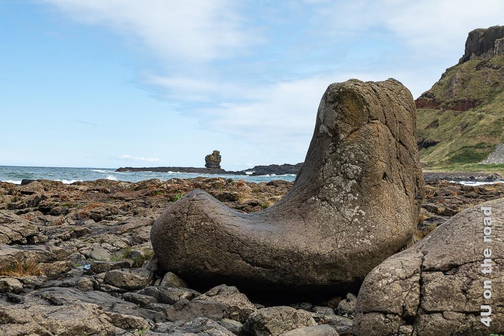 Bild Giants Causeway - steinerner Sitz zeigt im Vordergrund einen Felsen in Sesselform, im Hintergrund weitere Felsen, das Meer und ein Felsturm.