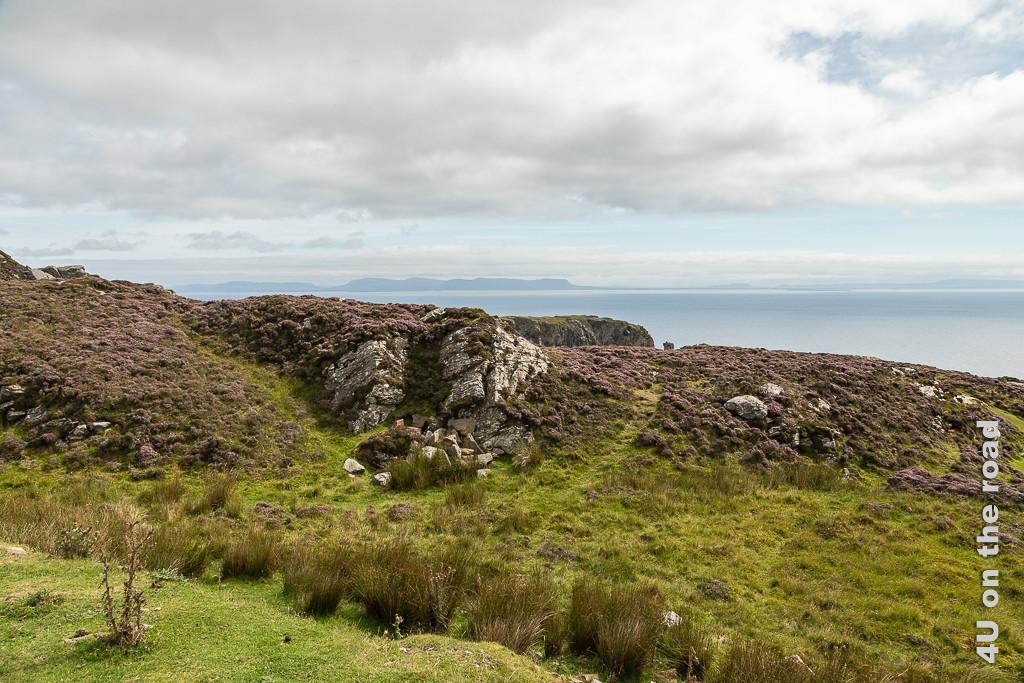 Bild Alter Wachturm - Slieve League zeigt in der Ferne den alten Wachturm. Im Vordergrund sind Felsen und Heidekraut zu sehen. Am Ende des Horizontes ragt eine Bergkette aus dem Meer in den Himmel.