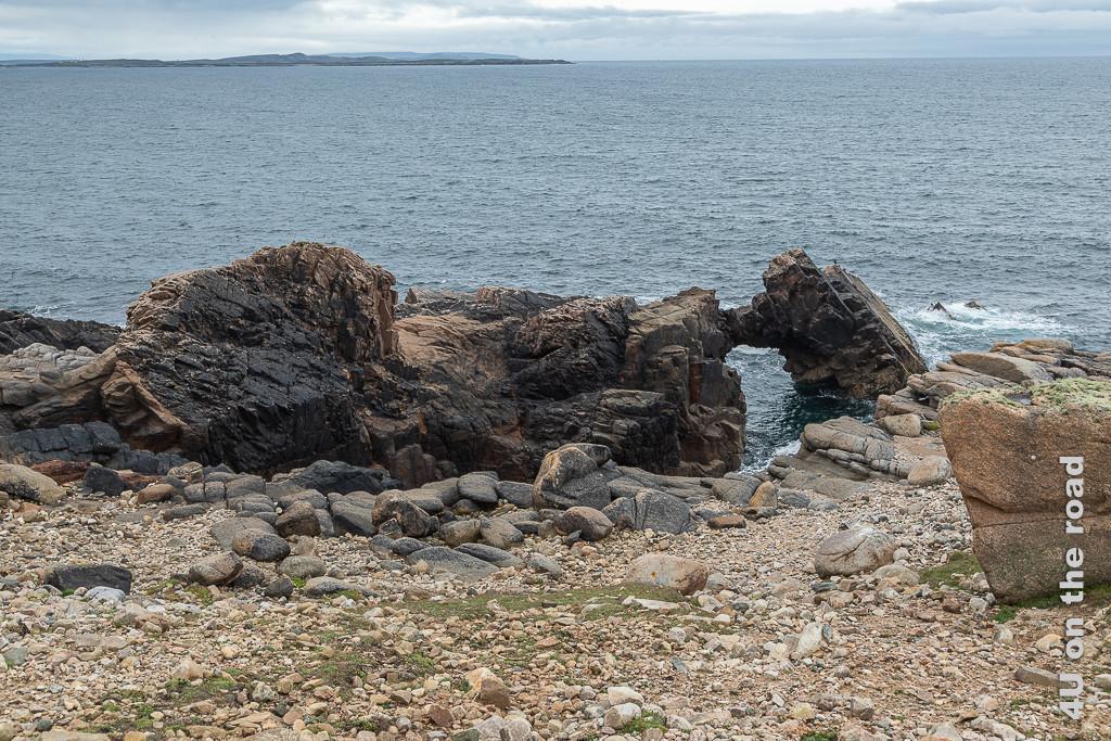Bild kleines Tor am Strand zeigt den steinigen Strand mit einer Felsader in der das Wasser einen Bogen ausgewaschen hat.