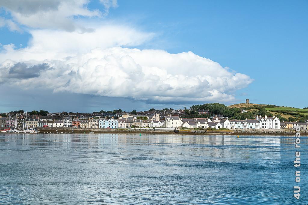 Bild Blick auf Portaferry vom Wasser des Strangford Lough aus gesehen, zeigt die bunten Häuser an der Wasserfront. Im Hintergrund erhebt sich ein Hügel mit Turm. Links erkennt man den Segelhafen.