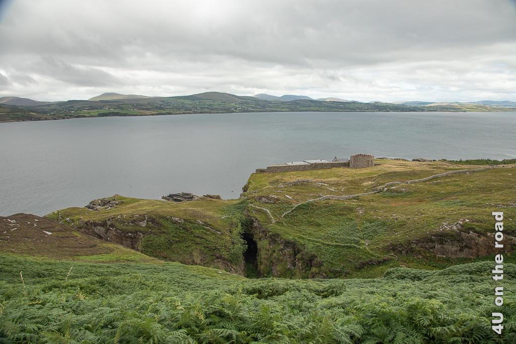 Bild Fanad Island - Blick auf die vielfältige Küste zeigt ein grosses Loch vor der Küste. Ob es einen Durchgang zum Meer gibt ist nicht zu sehen. Die Reste eines alten Turmes schmiegen sich an eine Mauer hinter der moderenere Dächer zu erkennen sind.