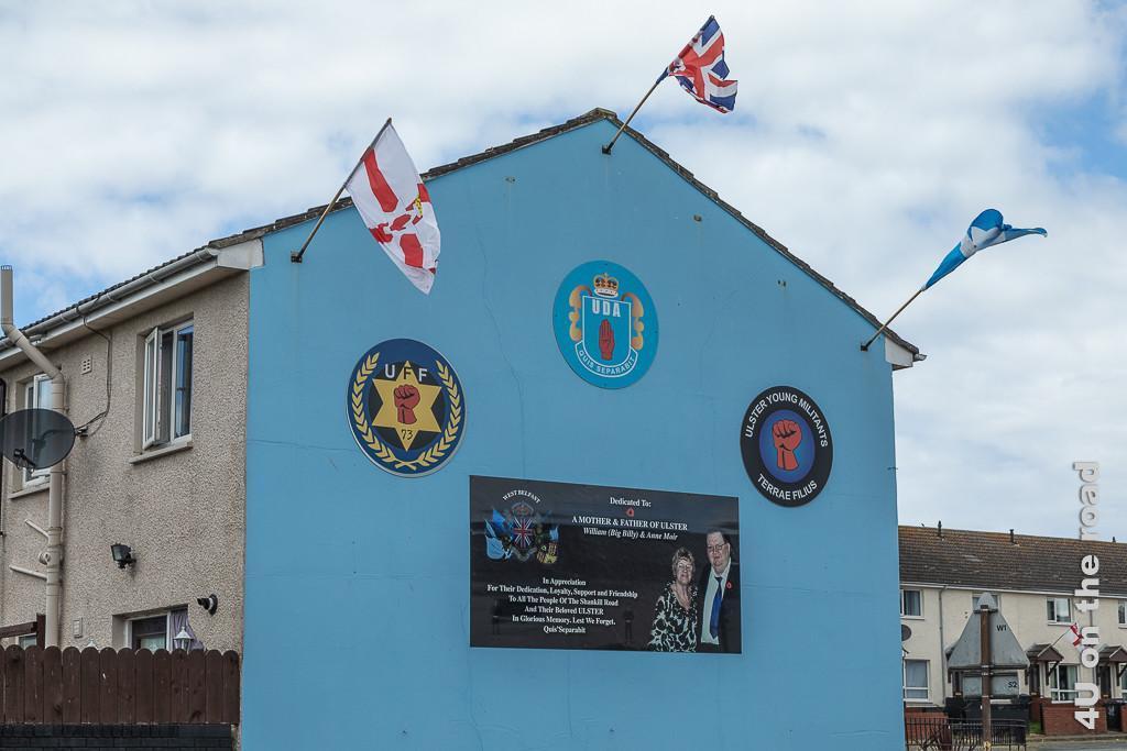 Bild Flaggen an der Erinnerungsfassade Black Taxi Tour Belfast zeigt auf hellblauem Hintergrund drei runde Logos und ein grosses Foto eines Ehepaars, welchem für seine Unterstützung gedankt wird