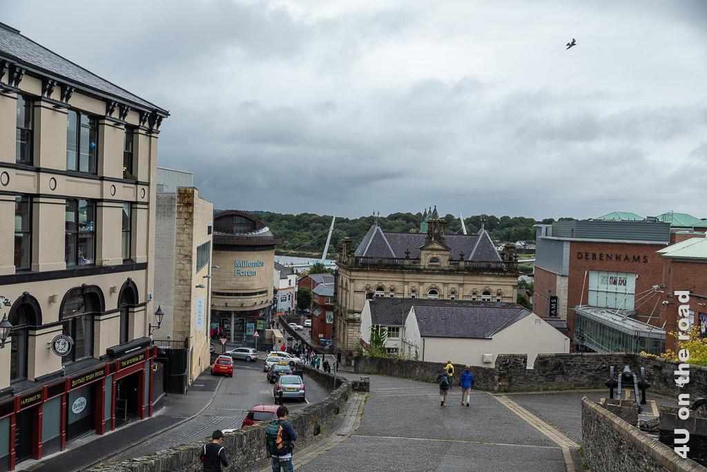 Bild Aufgang zur Stadtmauer - Derry-Londonderry zeigt den breiten geteerten Aufgang zur Stadtmauer. Vor den Zinnen steht eine Kanone. Links neben der Stadtmauer verläuft eine Strasse und parken Autos. Geschäftshäuser stehen rechts und links von der Stadtmauer.