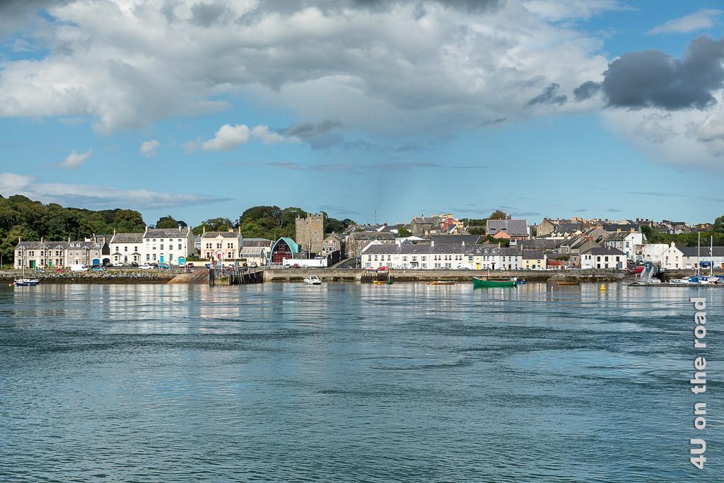 Bild Blick auf Portaferry kurz vorm Anleger zeigt ein altes breites turmförmiges Gebäude, dafor erhebt sich ein Gebäude in Form eines halben Schiffsrumpfes mit auffällig türkisfarbenem Dach. Rechts und links stehen farbige Häuser.