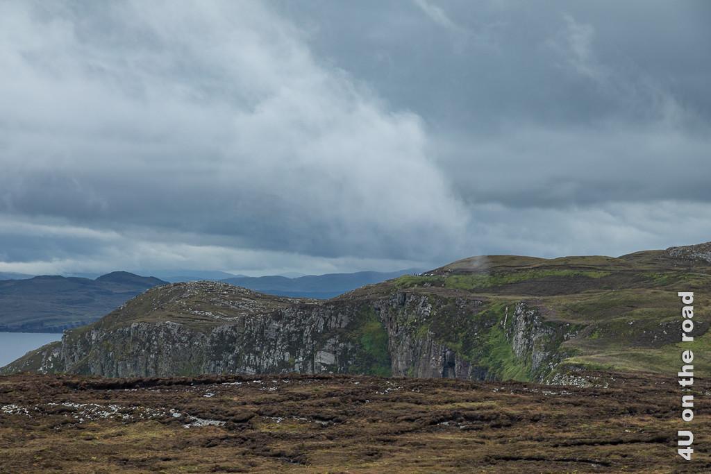 Bild Raue Moorlandschaft und Klippen am Horn Head zeigt im Vordergrund braunes Moor, dahinter erheben sich Felsklippen, die teileweise an den Seiten grün bewachsen sind und der Kuppen wieder moorig sind.