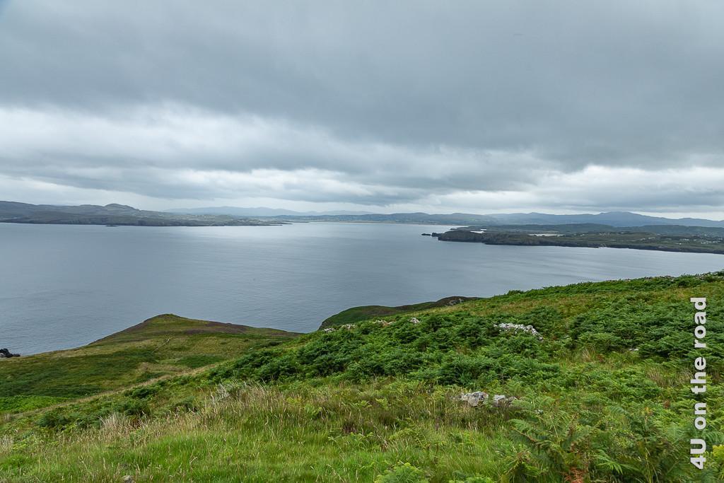 Bild Am Horn Head zeigt grüne farbewachsene Klippen, Wasser, Inseln und Land.