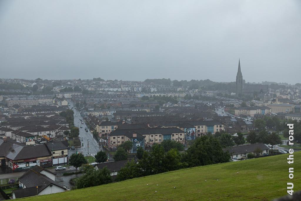 Bild Blick von der Stadtmauer Derry-Londonderry auf Häuser mit bemalten Fronten zeigt ein Häusermeer in Reih und Glied. Links teilt eine Strasse das Häusermeer, links erhebt sich eine Kirche.