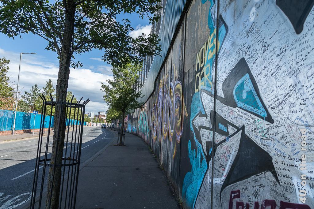 Bild Der Friedenswall, Black Taxi Tour Belfast zeigt den mit Graffiti besprayten unteren Teil der Mauer aus Betonelementen neben der Strasse. Auf den Betonelementen sind noch stabile Metallzaunelemente befestigt.