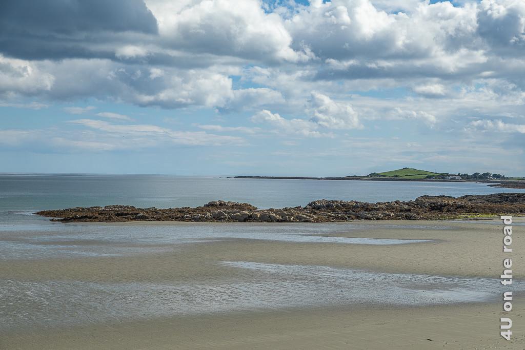 Bild Strandspaziergang auf der Ards Peninsula zeigt eine Strand bei Ebbe und eine Felszunge, die ins Meer ragt. Im Hintergrund ist eine weitere Bucht zu erkennen, an deren Ende sich ein grüner, spitzer Hügel erhebt