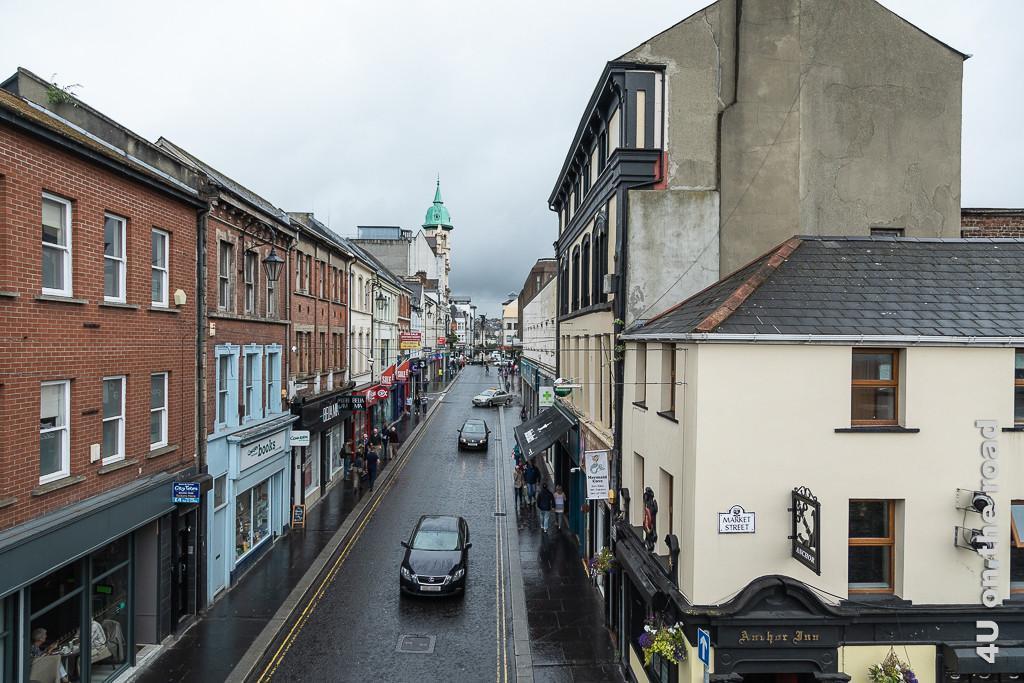 Bild Blick von der Stadtmauer Derry-Londonderry in eine Geschäftsstrasse zeigt rechts und links Wohnhäuser in deren Erdgeschoss sich Geschäfte befinden. Ein Kirchturm ragt heraus, Menschen und Autos sind unterwegs.