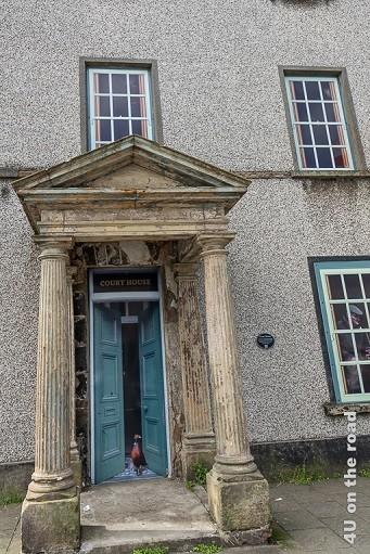 Bild Bushmills - Court House zeigt den Eingang mit Säulen. Aus der leicht geöffneten Tür kommt ein Fasan gelaufen. Fasan und Tür sind Fototapete. Im ersten Moment sieht es echt aus. Hinter den Fenstern sind Leute zu sehen (Fototapete).