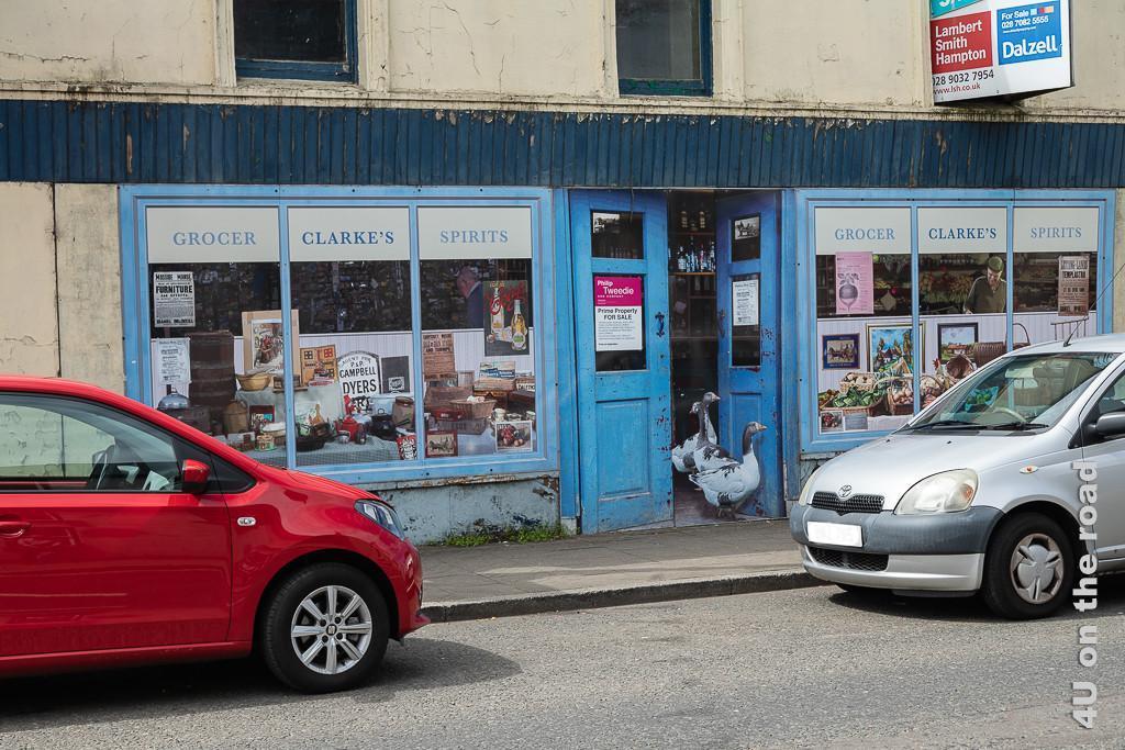 Bild Bushmills - Crocerie zeigt ein leerstehendes Haus, dessen Schaufenster und Tür mit Fototapete im Stil eines alten Lebensmittelladens gestaltet sind. Aus der geöffneten Tür kommen Gänse heraus, vor dem Geschäft parken Autos.