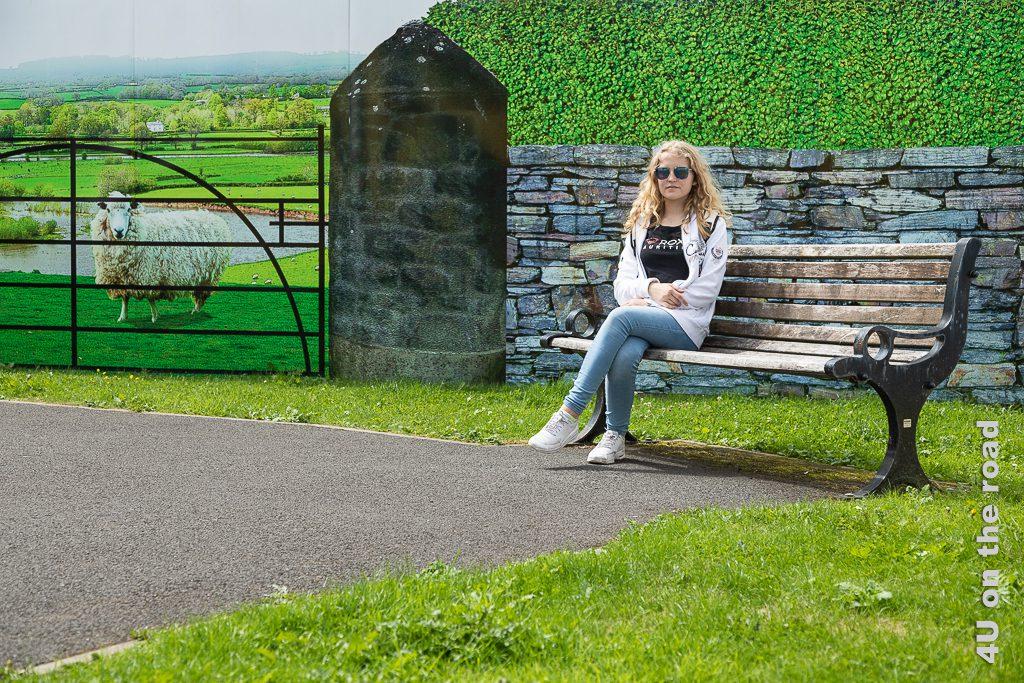 Bushmills - Fake Park, der Hintergrund ist Fototapete zeigt Morgaine auf Parkbank umgeben von Gras sitzend. Im Hintergrund zieht man Steinmauer, Hecke, Eisentor, Schaf und Landschaft. Dies ist ebenfalls eine Fototapete, die eine hässliche Brache überdeckt.