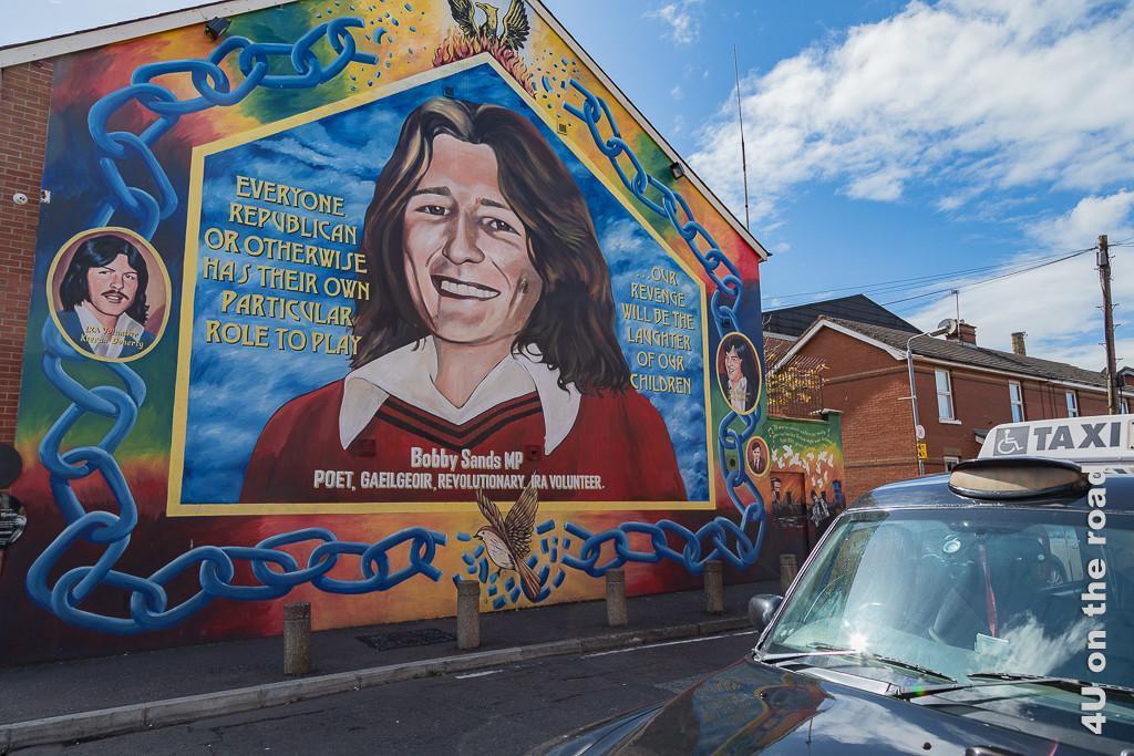 Bild Erinnerung an den Hungerstreik, Black Taxi Tour  Belfast zeigt das Bild von Bobby Sands umgeben von gesprengten Ketten. Rechts und links sind die Portraits der beiden Mitstreikenden. Die Fassade ist farbenprächtig. Am Giebel steigt Phönix aus dem Feuer.