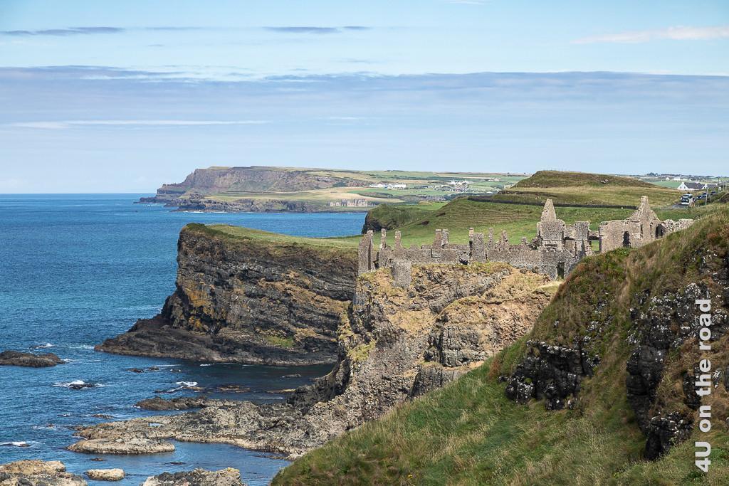 Bild Dunluce Castle zeigt die auf einer Klippe thronende Ruine, im Hintergrund weitere Klippen und Buchten
