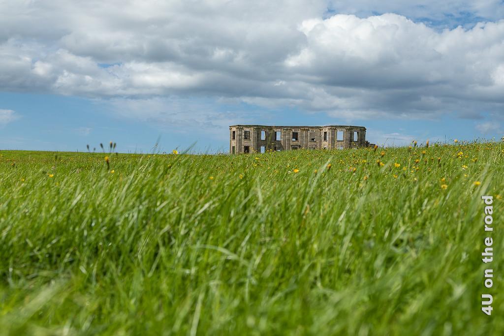 Bild Downhill House zeigt die Ruine des ehemaligen Landsitzes von unten aufgenommen. Im Vordergrund saftig grünes Gras.