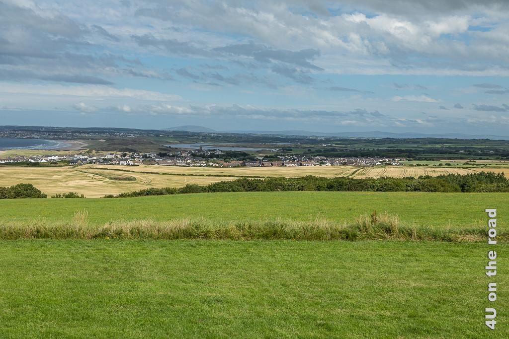 Bild Blick von Downhill House zeigt von vorn nach hinten von erhöhter Position, grünes Gras, grüne Hecken, gelbe Felder, Häuser, links das Meer mit Strand durch eine kleine Landbrücke getrennt von einem Fluss, dahinter weitere Häuser und höhere Hügel und blauer Himmel mit einigen Wolken..