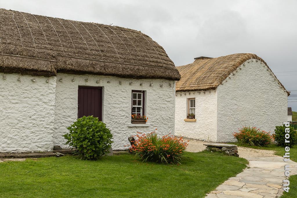 Bild Cottages - Glencolmcille Folk Village zeigt den Weg zu zwei im 90° Winkel aufeinander zulaufende Cottages mit Strohdach. Die Dächer sind rundherum mit hängenden Steinen beschwert.