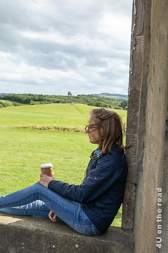 Bild Fenster im Downhill House zeigt Gwendolyn im Fensterrahmen sitzend mit Blick auf den in einiger Entfernung stehenden Turm.