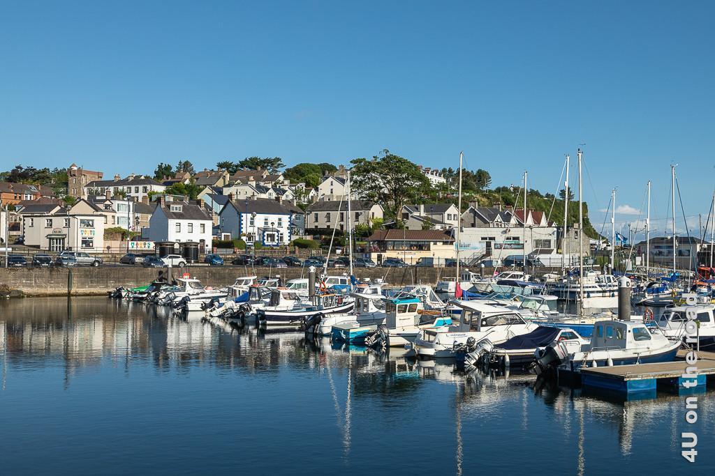 Bild Ballycastle vom Hafen aus gesehen zeigt das Hafenbecken mit kleinen Schiffen und die Häuser, die im Hintergrund den Hügel hinaufwachsen
