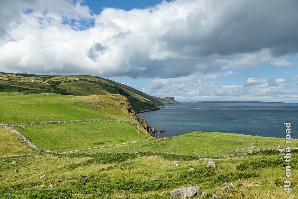 Bild Sicht beim Aufstieg zum Torr Head zeigt die grünen Klippen, welche mehr oder weniger Steil zum Wasser hin abfallen. In der Ferne sieht man Schottland.