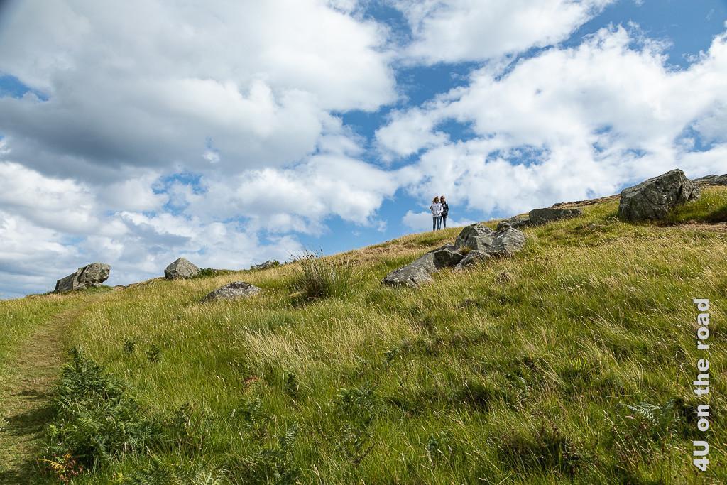 """Bild Allein mit dem Wind unterhalb des """"Gipfels"""" des Torr Heads zeigt die von Gräsern und Felsen bedeckte Flanke des Hügels. Vor dem Horizont stehen die Mädels mit im Wind fliegenden Haaren."""