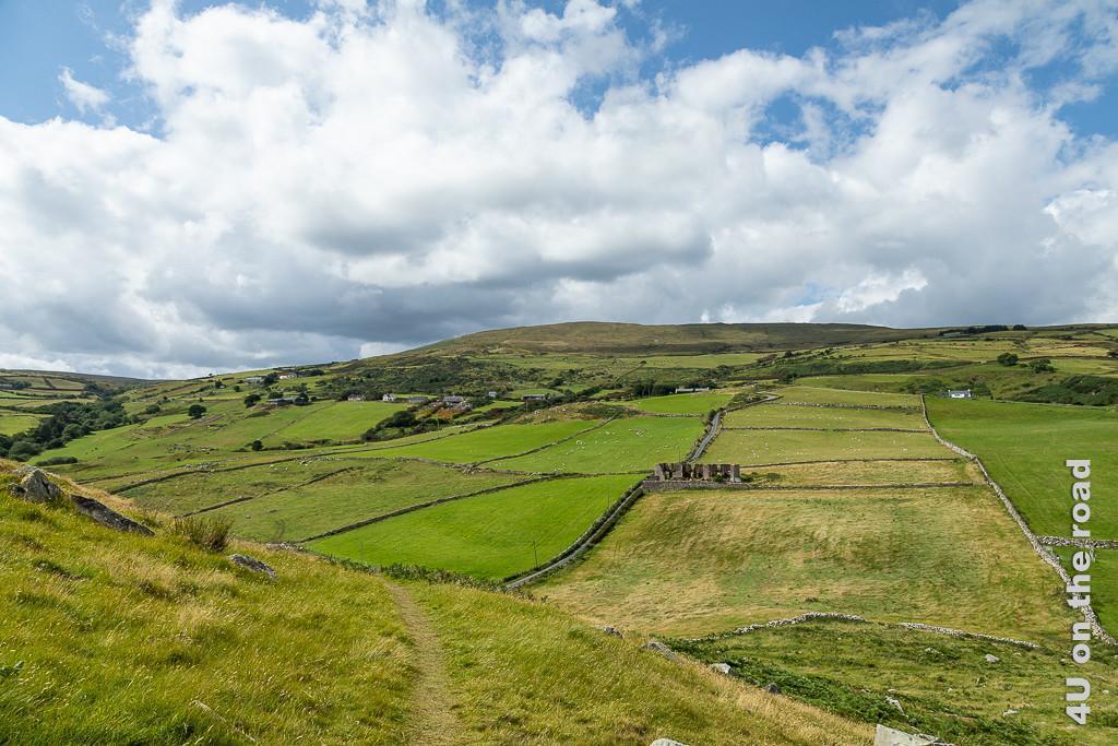 Bild Blick vom Torr Head zeigt die von Mauern und Strassen durchzogene, ansteigende Landschaft mit Ruine.