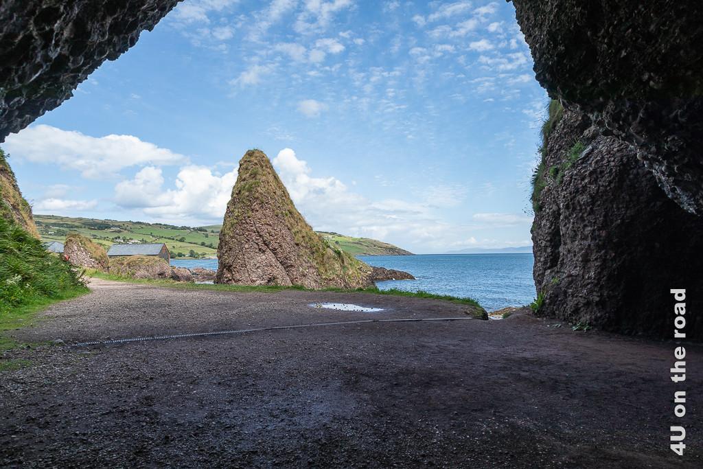 Bild Cushendun - Blick aus dem Inneren der Höhle zeigt wie einen Zahn aufragenden kleineren Hügel vor dem Meer. Um Hintergrund Küstenlandschaft