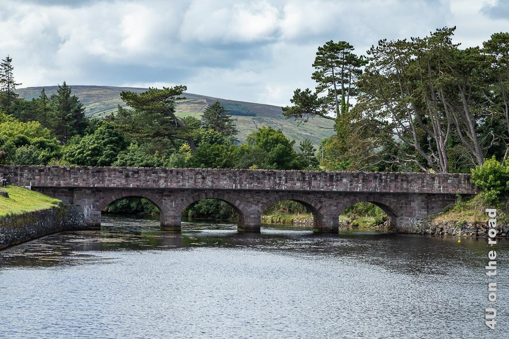 Bild Cushendun - Brücke zeigt eine schöne steinerne, flache Brücke mit 4 Bögen über den Fluss. In Hintergrund alte Bäume und Berge.