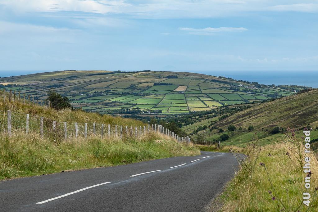 Bild Landschaft unterwegs zeigt einen sehr markant durch Mauern und Hecken unterteilten Hügel mit unterschiedlich farbenen Flächen.