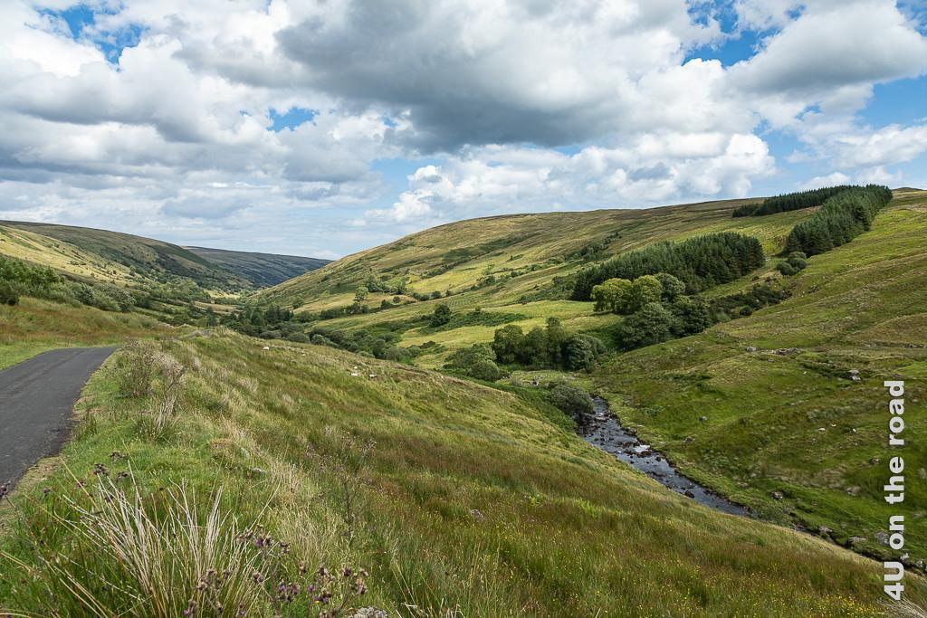 Bild Ein schönes Tal, zeigt ein Tal von sanften Hügeln gerahmt mit kleinem Bach. Die Landschaft wirkt sehr moorig.