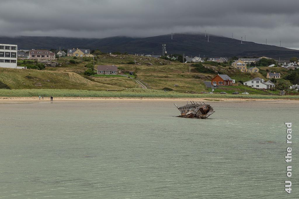 Bild Wrack am Meer bei Bunbeg zeigt die Hälfte eines hölzernen Schiffsrumpfes im Wasser. Im Hintergrund sieht man farbige Häuser und Windräder auf einem Hügel halb in den Wolken