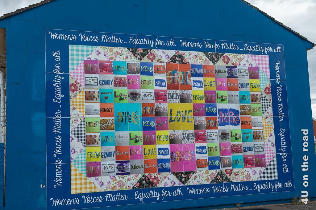 Bild Womans Quilt, Black Taxi Tour Belfast zeigt auf mittelblauer Hauswand das Bild eines riesigen, farbenprächtigen Flickenteppichs.