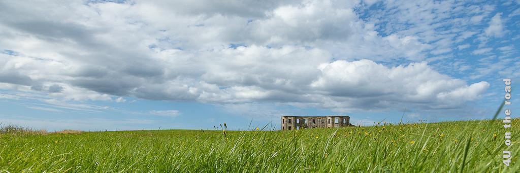 Downhill Haus, zeigt die Ruine am Horizont, wo Himmel und Wiese verschmelzen.