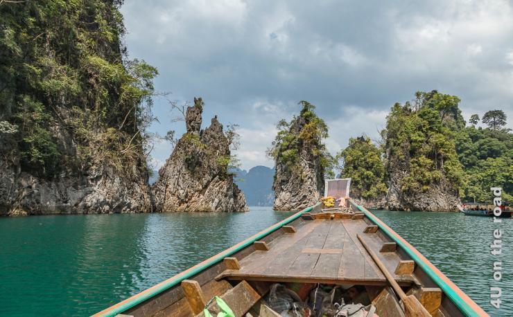 Bild Auf dem Cheow Lan Lake zeigt die Spitze des Longboats, welche auf eine Gruppe schlanker aus dem Wasser ragenden Felsen zeigt. Die Felsen sind mit Büschen bewachsen.