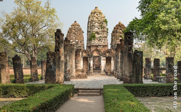Bild Tempel im Historical Park - Sukhothai zeigt im Hintergrund den Tempel mit drei Türmen. Der Weg hin ist gesäumt von niedrigen Hecken und hohen Säulen. Rechts und links stehen niedrigere Säulen und Bäume.