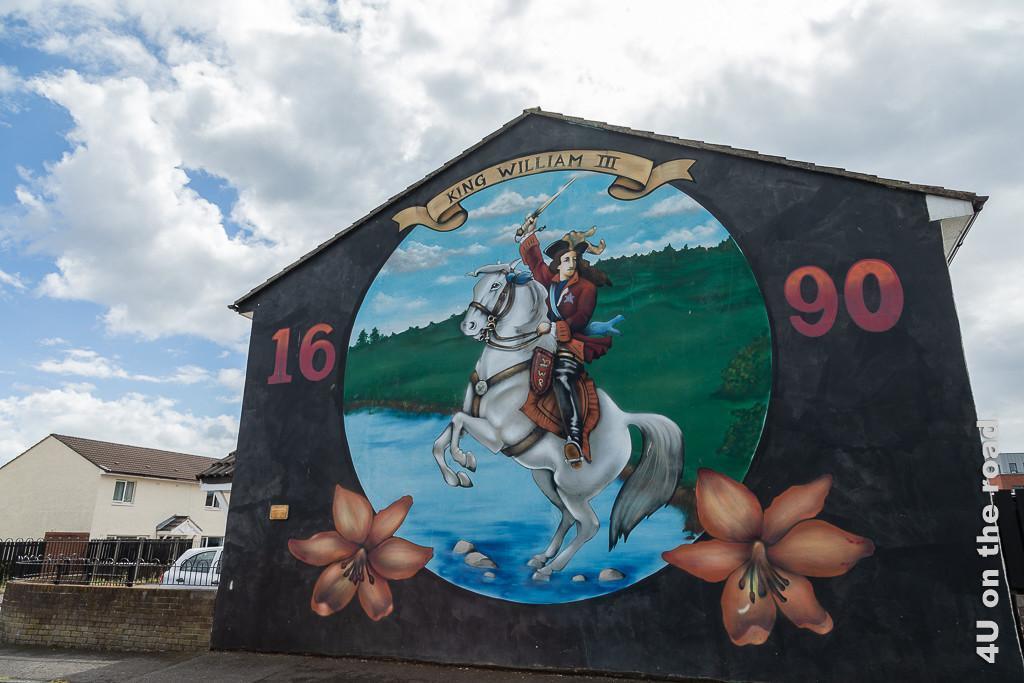 Bild Hausfassade mit King William Bild, Belfast zeigt in einer Kugel auf schwarzem Hintergrund King William zu Pferd im Wasser. Im Hintergrund ein grüner Hügel und Himmel. Die Jahreszahl 1690, sowie zwei Lilienblüten zieren die Fassade.