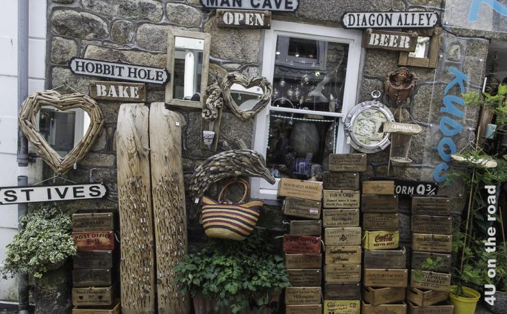 Das Bild zeigt die Auslagen eines Ladengeschäfts in Südengland, die von verschieden beschrifteten Holzkisten über Taschen, Tieren aus Strandgut bis hin zu Schildern alles verkauft.