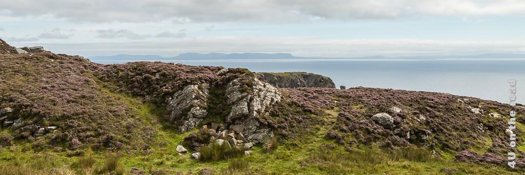 Blick von den Slieve League zeigt die Heidekraut bewachsenen Klippen, das Meer und die Silhouette von Felsen im Hintergrund.