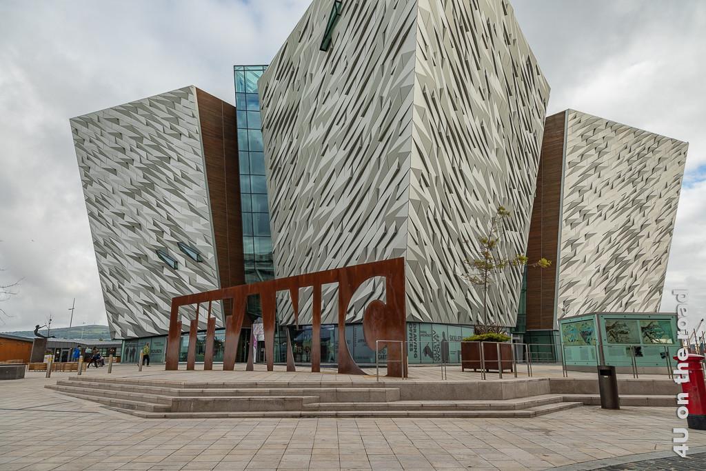 Titanic Museum, Belfast zeigt den Vorplatz und das Museum mit dem Schiffsbug in drei Himmelsreichtungen, die mit ihrer glänzenden Kristallstruktur an einen Eisberg erinnern. Davor der grosse rostige Schriftzug.