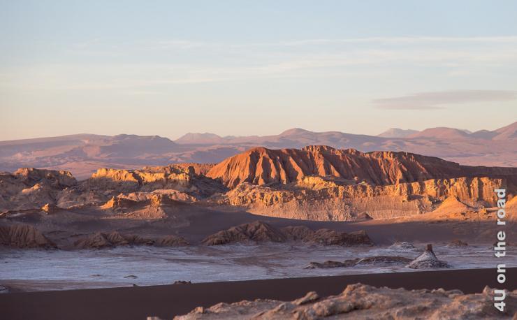 Bild zeigt die orange angeleuchteten Felsen des Valle de la Luna. Der Vordergrund liegt bereits im Schatten. Das Salz leuchtet weiss.