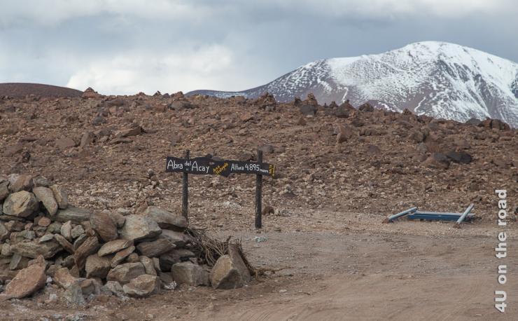 Bild zeigt die Höhenmarkierung des Passes Abra del Acay mit 4.895 m Höhe. Im Hintergrund verschneite Berge.