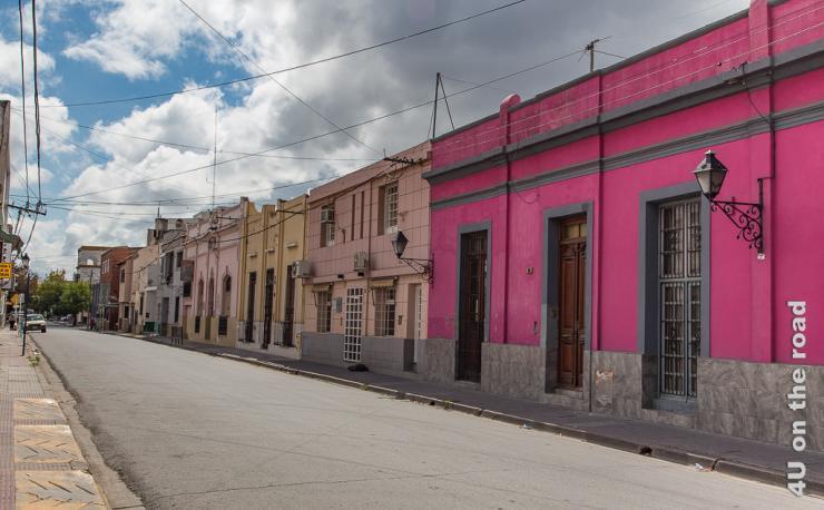 Bild zeigt eine Strasse mit farbigen Häusern von kräftigem Pink bis zu zartem Rosa.