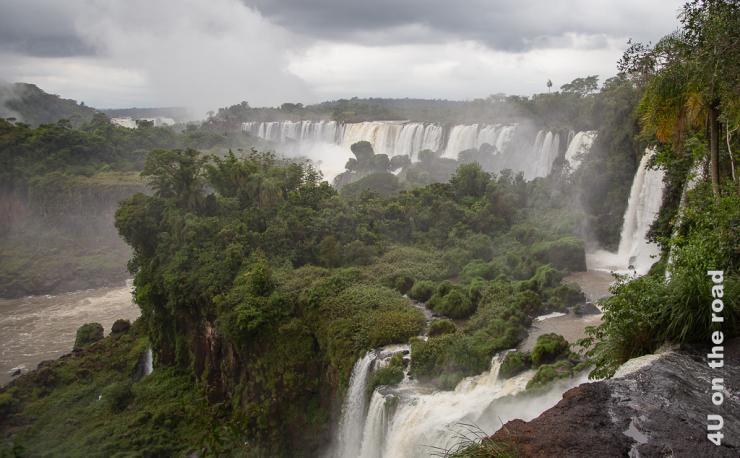Bild zeigt grünen Dschungel mit Wasserfällen. Im Hintergrund fällt das Wasser über eine breite Kannte. Im Vordergrund sieht man eine weitere Etage der Wasserfälle.