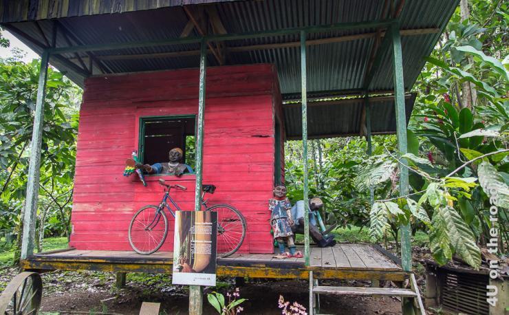 Bild zeigt ein früher typisches Haus mit einem Raum und einer überdachten Veranda auf Stelzen. Auf der Veranda steht ein Fahrrad.